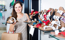 Young woman customer selecting shoes in footgear center. Portrait of young woman customer selecting shoes in footgear center Royalty Free Stock Photos