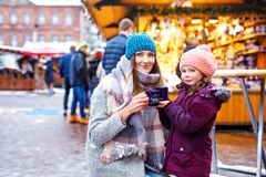 Young woman and cute kid girl with cup of steaming hot chocolate or children punch. Happy kid girl and young beautiful women with cup of steaming hot chocolate royalty free stock photography