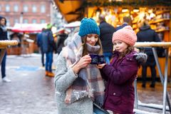 Young woman and cute kid girl with cup of steaming hot chocolate or children punch. Happy kid girl and young beautiful women with cup of steaming hot chocolate royalty free stock images