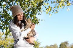 Young woman with cute stray cat outdoors. Space for text stock images