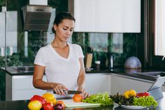 A young woman spends time at home, in the kitchen and in the roo. The young woman cuts vegetables in the kitchen with a knife and laptop on the table. Vegetable Royalty Free Stock Photography