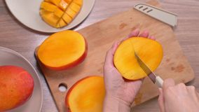 Young woman is cutting a beautiful fresh juicy mango to eat on a wooden table and chopping board in the kitchen, close up , 4K. Video shot stock video footage