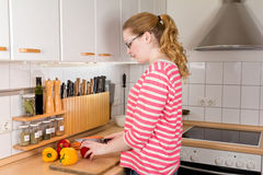 Young woman cutting bell peppers Stock Photos