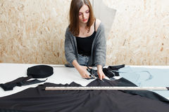 Young woman cutting black fabric in workshop Royalty Free Stock Images