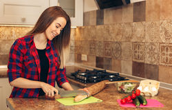 Young woman cutting bread in kitchen. Indoor shot of female in kitchen during morning. Focus on woman cutting bread, preparing breakfast Stock Image