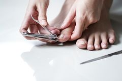 Young WomanCutting Foot Fingernail Stock Images