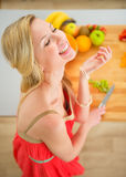 Young woman cutting fruits in kitchen Stock Image