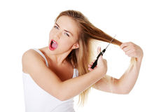 Young woman cutting her long hairs Royalty Free Stock Images