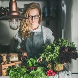 Young woman cutting herbs and vegetables in kitchen, square crop stock photography