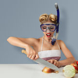 Young woman cutting onion in diving mask. Young blonde woman cutting onion in diving scuba mask for protect eyes stock photo