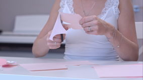 Young woman cutting out paper butterfly stock video