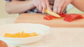 Young woman cutting paprika stock footage