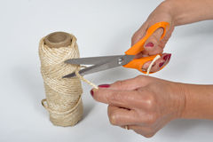 Young woman cutting a piece of string Royalty Free Stock Photo