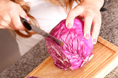 Young woman cutting red Cabbage Royalty Free Stock Image