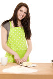 Young woman cutting shortening for baking. Young happy woman cutting butter for baking on white background Royalty Free Stock Images