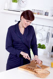 Young woman cutting a slice of bread in her kitchen Royalty Free Stock Images