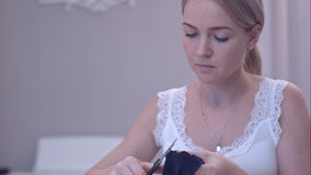 Young woman cutting thread with scissors while sewing. Close up shot. Professional shot on BMCC RAW with high dynamic range. You can use it e.g. in your stock video