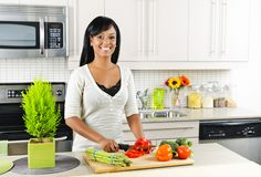 Young Woman Cutting Vegetables In Kitchen Royalty Free Stock Photo