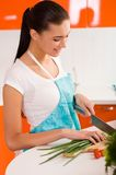 Young woman cutting vegetables in a kitchen Stock Image