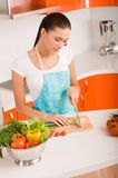 Young woman cutting vegetables in a kitchen Royalty Free Stock Image