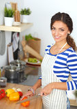 Young woman cutting vegetables in kitchen Stock Images