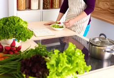 Young woman cutting vegetables in the kitchen.  Stock Image