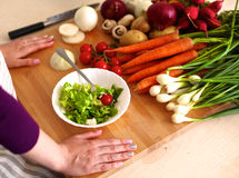 Young woman cutting vegetables in the kitchen.  Royalty Free Stock Image