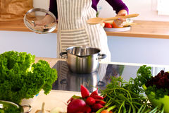 Young woman cutting vegetables in the kitchen.  Royalty Free Stock Photography