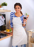 Young woman cutting vegetables in kitchen, holding Royalty Free Stock Photography