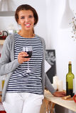 Young woman cutting vegetables in kitchen, holding. A glass of wine Stock Photography