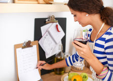 Young woman cutting vegetables in kitchen, holding. A glass of wine Royalty Free Stock Image