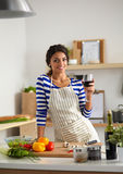 Young woman cutting vegetables in kitchen, holding Stock Photo