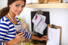 Young woman cutting vegetables in kitchen, holding. A glass of wine Stock Photo