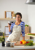 Young woman cutting vegetables in kitchen, holding. A glass of wine Royalty Free Stock Photo