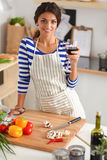 Young woman cutting vegetables in kitchen, holding Stock Photography