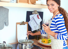 Young woman cutting vegetables in kitchen, holding a glass of wine Stock Photography