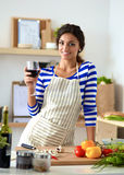 Young woman cutting vegetables in kitchen, holding a glass of wine Stock Photos