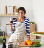 Young woman cutting vegetables in kitchen, holding a glass of wine. Young woman cutting vegetables in kitchen ,standing Royalty Free Stock Image