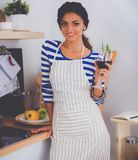 Young woman cutting vegetables in kitchen, holding a glass of wine.  Royalty Free Stock Photography