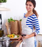 Young woman cutting vegetables in kitchen, holding a glass of wine.  Royalty Free Stock Photos