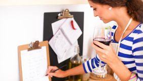 Young woman cutting vegetables in kitchen, holding a glass of wine.  Stock Photography