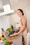 Young woman cutting zucchini in the kitchen Stock Photo