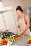 Young woman cutting zucchini in the kitchen Stock Image