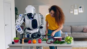 Young woman and a cyborg cook dinner together. Robot, cyborg and human concept. Young woman and a cyborg cook dinner together. 4K stock video footage