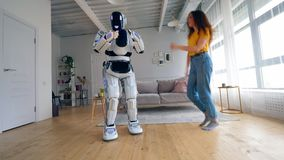 Young woman and a cyborg are dancing happily stock footage