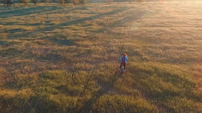 Young woman cycling bike in countryland area over sunset sky background stock video footage