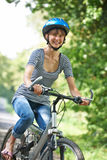 Young Woman Cycling On Country Road Stock Photography