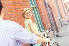 Young woman cycling with her boyfriend Royalty Free Stock Images