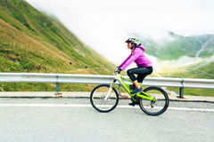 Young Woman Cycling. Shot taken in Switzerland, near Rhone Glacier and Furka Pass Royalty Free Stock Image