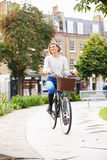 Young Woman Cycling Through Urban Park Royalty Free Stock Image